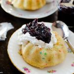 These moist Mini Bundt Cakes are made with confetti sprinkles and served with whipped cream and homemade blueberry compote. Perfect as an elegant dessert.