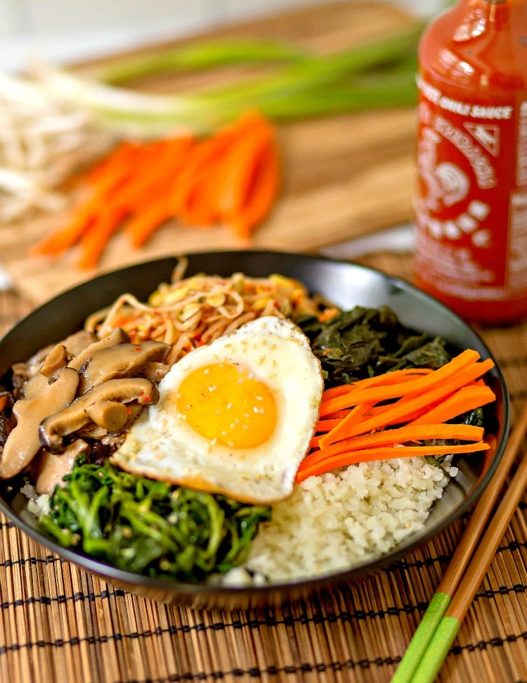 This amazing Korean Cauliflower Bibimbap recipe is delicious, low-carb, keto friendly, and easy to make. The perfect quick vegetarian weeknight dinner idea. Black bowl, bobimbap, sriracha