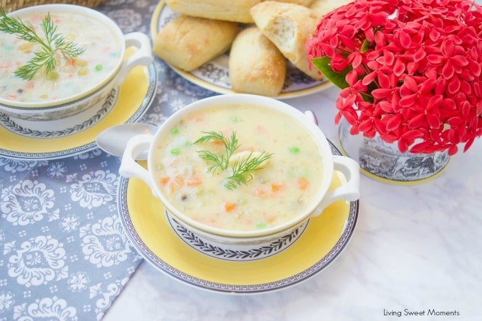 This creamy Potato Dumpling Soup recipe is the perfect hearty vegetarian soup for winter. 2 bowls of soup with red flowers and fresh baked rolls