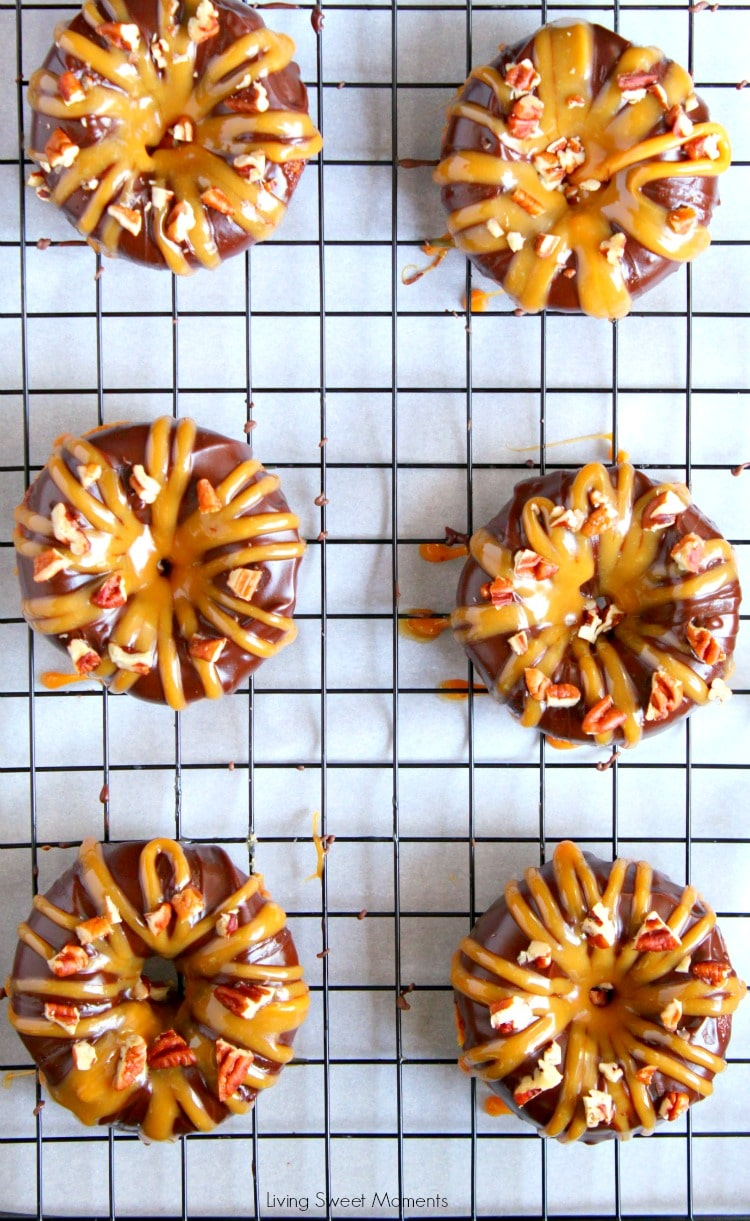 These decadent Baked Turtle Donuts are are glazed with chocolate, sprinkled with toasted pecans and drizzled with sweet caramel. Sheet pan with donuts on top