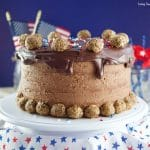 This colossal Peanut Butter Chocolate Cake recipe is made from scratch and is garnished with peanut butter chocolate truffles rolled in peanut butter & cocoa pebbles cereal