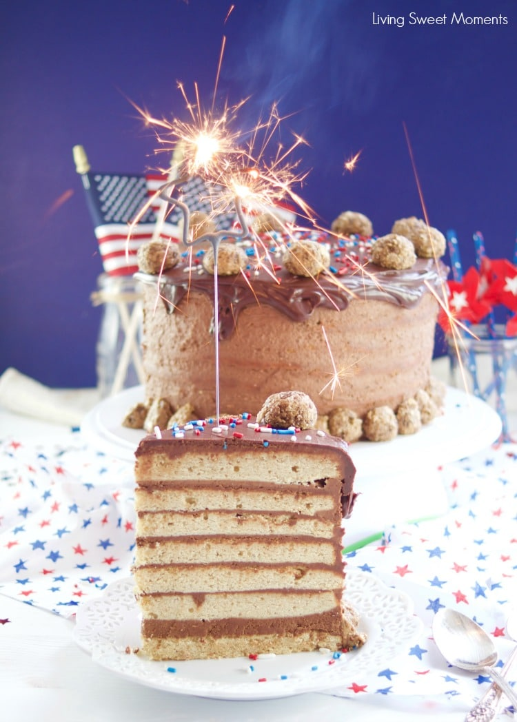 This colossal Peanut Butter Chocolate Cake recipe is made from scratch and there's a slice with a sparkler on top. Beautiful cake for celebrations