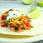 You won't believe how easy these Slow Cooker Shredded Chicken Tacos are to make. Serve in a warm tortilla with cheese, veggies, and sour cream